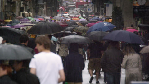 Slow motion footage of a street filled with people holding umbrellas Footage