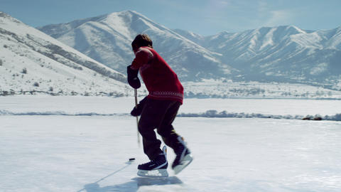 Young boy playing hockey at an outdoor rink Footage