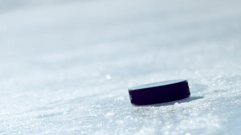 Hockey puck falling onto ice and being picked up by a gloved hand Footage