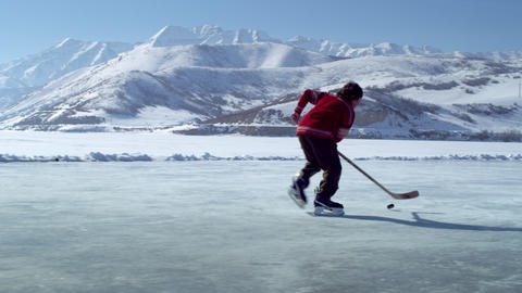Young boy dribbling a hockey puck at an outdoor ice rink Footage