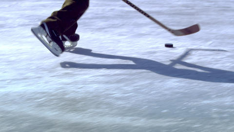 Close up of a boy dribbling a hockey puck at an outdoor ice rink Footage