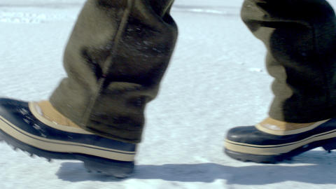Snow boots walking across a snow-covered ground Footage