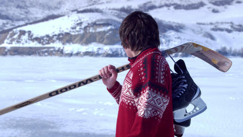 Young boy in a red sweater walking through snow with hockey gear Footage