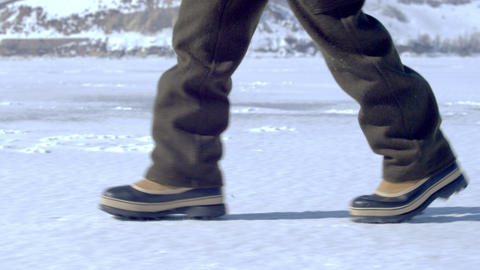 Snow boots walking across the snowy ground Footage