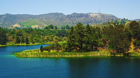 Long-distance static shot of reservoir, hills bearing Hollywood sign, houses Footage