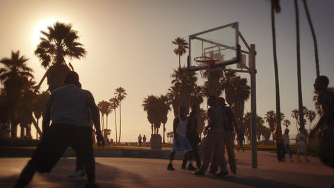 Slow motion lens flare shot of basketball players playing near Venice Beach, Cal Footage