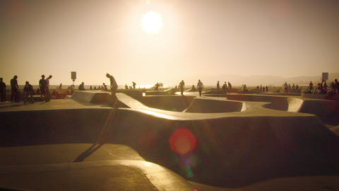 Slow motion lens flare shot of people at the skate park near Venice Beach, Calif Footage