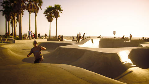 Slow motion lens flare shot of a skateboarder jumping over a ramp near Venice Be Footage