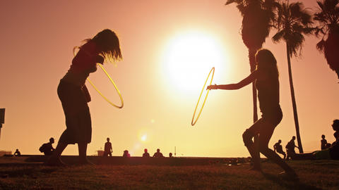 Lens flare shot of two women with hula hoops filmed in slow motion near Venice B Footage