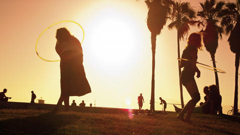 Slow motion shot of two women playing hula hoops with lens flare near Venice Bea Footage