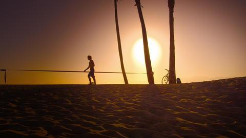 Lens flare shot of man walking beside slackline near Venice Beach, California Footage