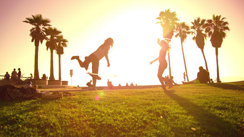 Slow motion lens flare shot of people strolling near Venice Beach, California Footage