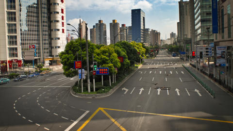 A view of a Chinese city with office buildings and orderly traffic stopping and  Footage