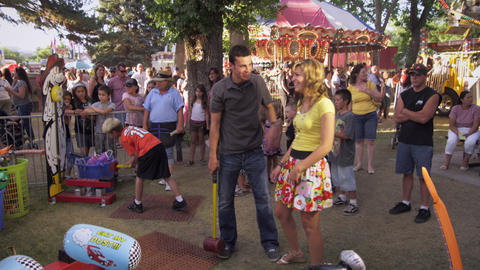 Shot of man and girl doing a hammer game at a carnival Footage