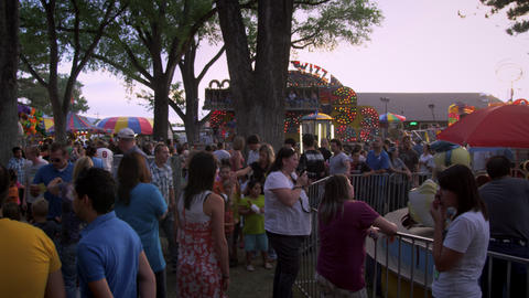 Panning shot of people walking through a fairground Footage