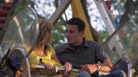 Close up shot of two couples riding a ferris wheel at a carnival Footage