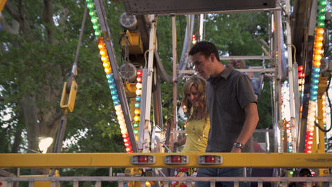 Shot of couple getting up and exiting a carnival ride Footage