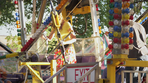 Shot of couple entering a carnival ride and sitting down in the chair Footage