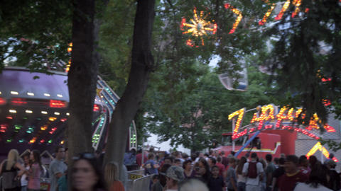 Panning shot of people and rides at a carnival Footage
