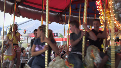 Slow motion shot of two couples riding around on a merry go round, laughing Footage