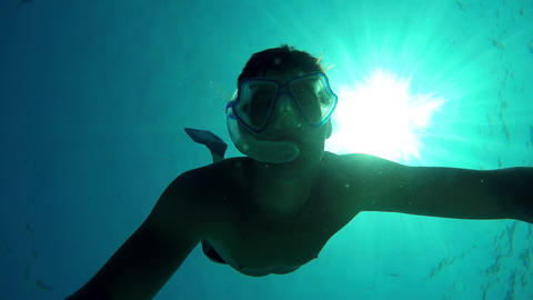 Young man swimming to the surface from the bottom of the sea Footage