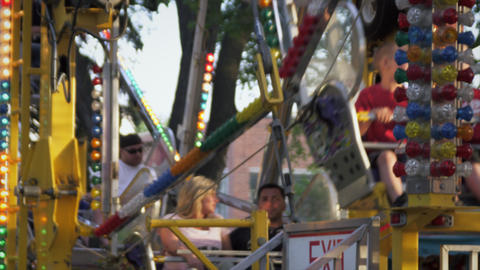 Close up of riders on a ferris wheel at it moves forward and up Footage
