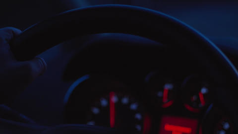 Hands on steering wheel, unfocused dashboard, night driving Live Action