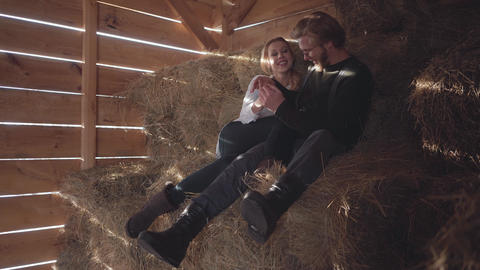 Pretty young couple sitting on the hay in the cold winter barn. Young farmer Live Action