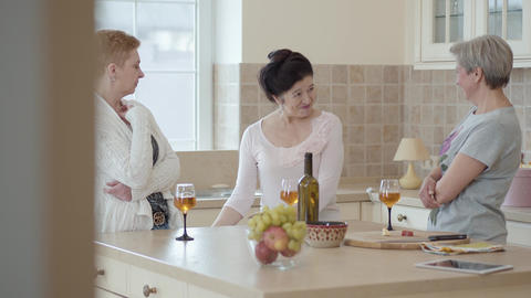 Three mature women communicating at home standing near modern table in the Footage