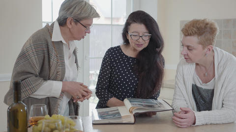 Senior woman with long black hair showing to friends her old photo album. Group Footage