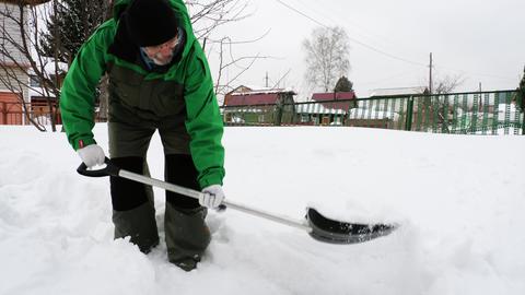 Elderly man shoveling snow in yard Live Action