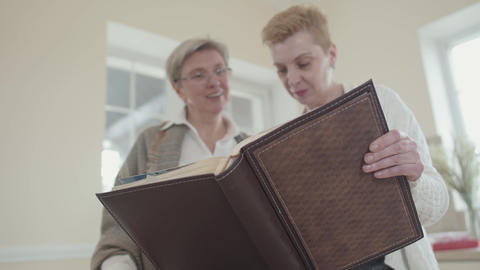 Two senior women holding big leather photo album and watching photos. Middle Live Action