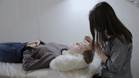 Masseur applies facial massage cream to a young girl in a beauty salon Live Action