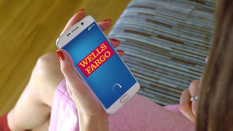 Young woman holding a cell phone with loading Wells Fargo mobile app. Conceptual Footage