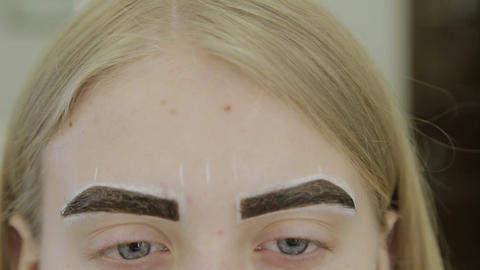 Beautiful young girl in a beauty salon is waiting for the eyebrow paint to be Footage