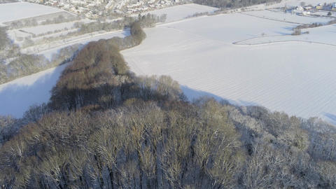 Snow covered winter landscape flying from forrest towards populated area in Germany close to Aachen Footage