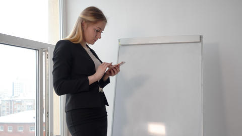 Business woman using mobile phone on flipchart in conference room Footage