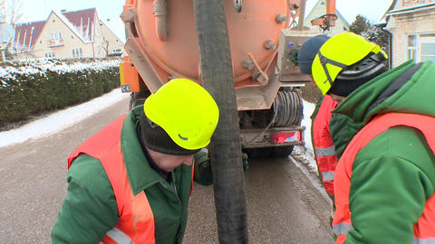 Sewerage removal team with special equipment working on street in winter season Live Action