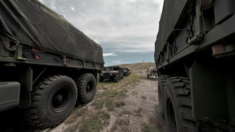 Time-lapse filmed between covered convoy trucks at a military training Footage