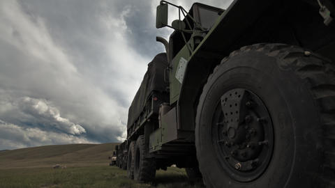 Dollying time-lapse of a stationary military convoy truck Footage
