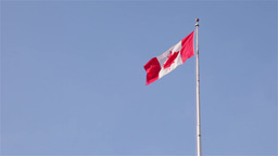 Canadian flag waving in the wind with blue sky Footage