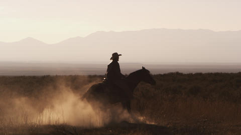 Slow motion silhouette shot of a cowboy riding a hourse in a circle Footage