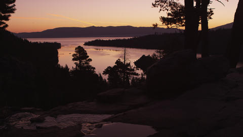 Static shot of Lake Tahoe at sunset with silhouetted trees and flowing river in  Footage