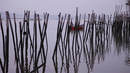 Small boat passing by wooden stakes belonging to the old fishing port Footage
