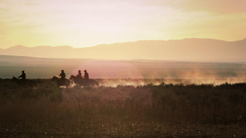 A group of 3 cowboys ride from camera right to camera left leaving a dust trail Footage
