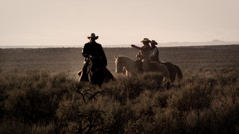 Slow motion shot of cowboys riding at dusk through brush Footage