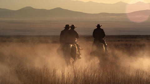 Slow motion dusk shot of cowboys riding towards mountains Footage