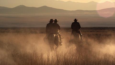 Slow motion dusk shot of cowboys riding towards mountains Footage