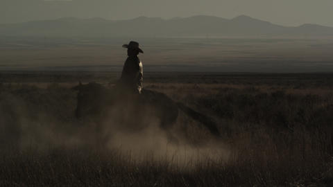 Slow motion static shot of cowboy riding a horse that is turning around Footage