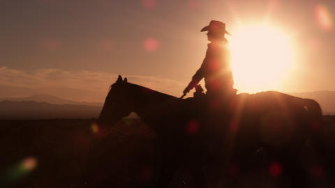 Slow motion shot of cowboy galloping in front of sunrise Footage